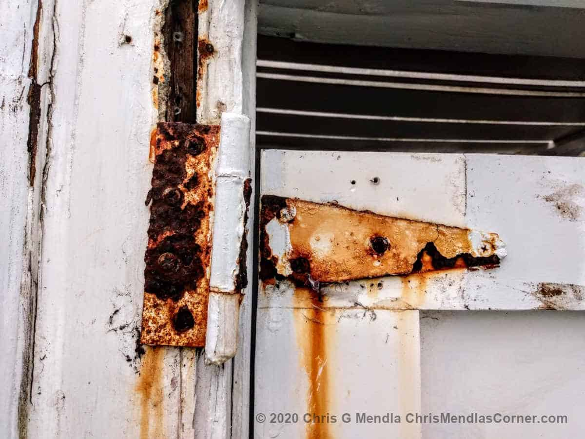 Failed rusty hinge on an outside shower door.